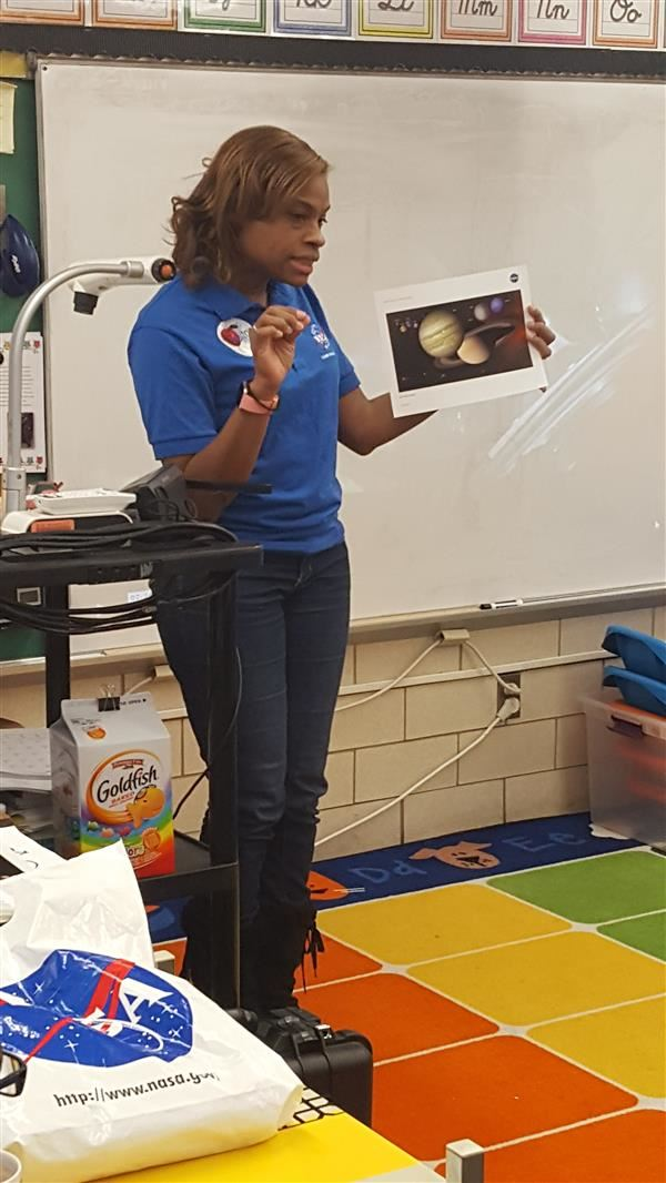 Mrs. Reid holding a photo of planets